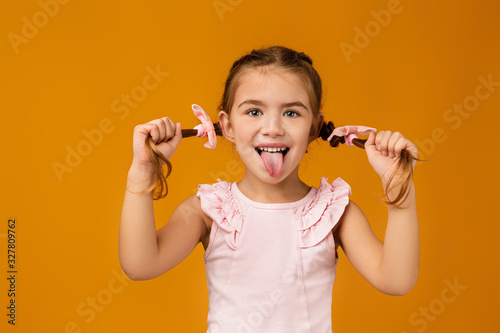 Obraz happy funny little child girl showing her tongue on yellow background. facial expression - fototapety do salonu