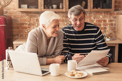 Obraz Smiling Senior Couple Reading Health Insurance Policy Contract In Kitchen Together - fototapety do salonu