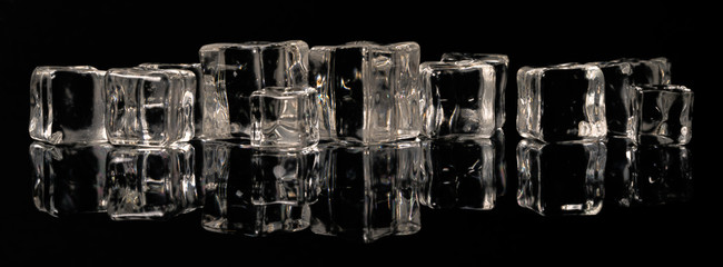 Ice cubes in a row on a black mirror surface with reflections isolated on black background.