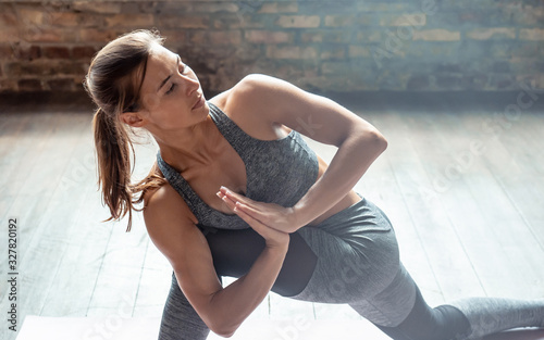 Photo Young sporty fit woman trainer do practice individual hatha yoga instructor training Parivrtta Anjaneyasana crescent lunge on knee prayer hands modern gym fitness workout healthy lifestyle concept