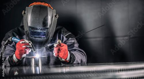Welder industrial worker welding with argon machine Canvas Print