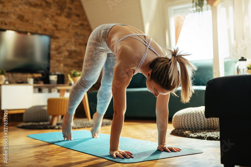 Foto Young woman doing stretching exercises at home.