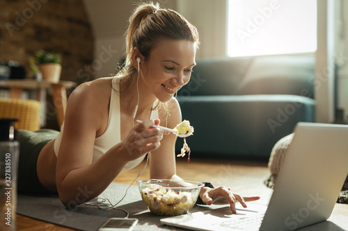 Happy sportswoman surfing the net on laptop while eating salad at home.