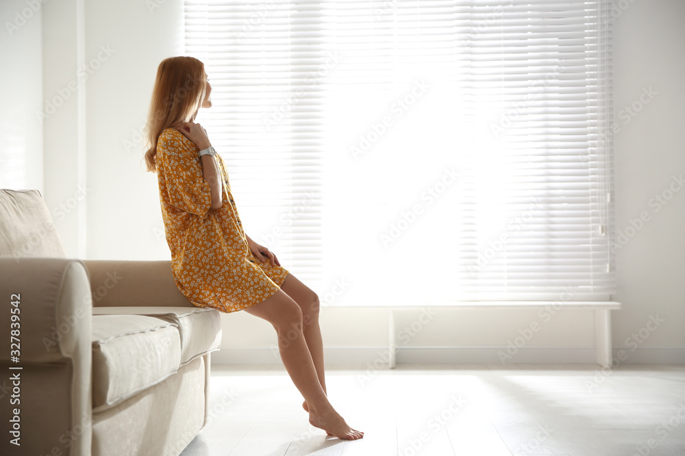 Fototapeta Young woman relaxing on couch near window at home. Space for text