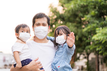 Asian Father Holding His Daughter And Son And All Of People Wear A Mask To Protect The Corona Virus And Pm 2.5 Dust In Air, Concept Of People Living In The Crisis Of Covid-19 And Air Pollution Problem