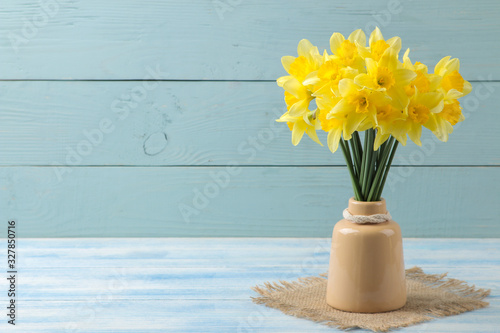 Cuadros en Lienzo Spring flowers, yellow daffodils in a vase on a blue wooden background