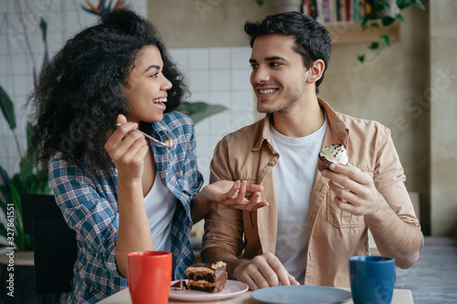 Fototapeta Happy multiracial friends communication together. Young lovely couple laughing, sitting in cafe. Beautiful African American woman and Indian man drinking coffee, eating tasty cake. First date concept obraz