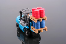 Miniature People : Engineer Driving Forklift And Lift Up Palette Which Have Four Red Drums And Four Blue Drums. Focus On Driver. Reflection Of Object. Industrial And Business Concept.