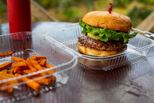 Tasty Grilled Beef Hamburger With Lettuce And A Pineapple In A Clear Plastic To Go Box At An Outdoor Restaurant. Served With Sweet Potato Fries