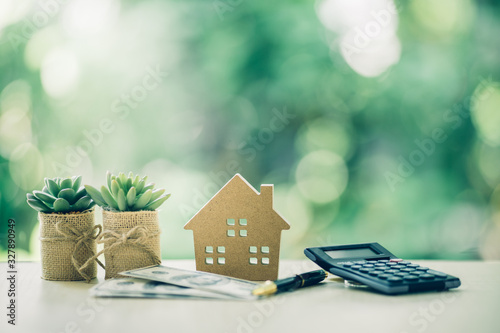 Property investment concept. Wooden house, dollar bill and calculator on table. Pen prepare planning savings money to buy a home, mortgage and real estate investment.