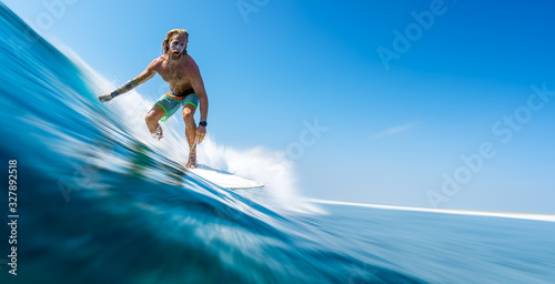 Fotomural Young man surfer with long hair surfs the fast and perfect ocean wave in Maldive