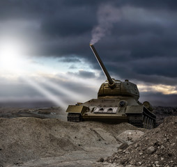 A tank approaching and climbing up a gravel hill with a smoking barrel in the rays of light from a clear spot in a dramatic cloudy sunset sky