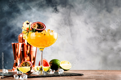 Obraz Alcoholic cocktail with fresh passion fruit with rosemary and ice. Gray wood background, bar tools, copy space - fototapety do salonu