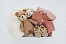 Box With Baby Stuff And Accessories For Newborn On Bed. Gift Box With Knitted Blanket, Clothes, Socks, Shoes And Toy. Baby Shower Concept.  Flat Lay, Top View