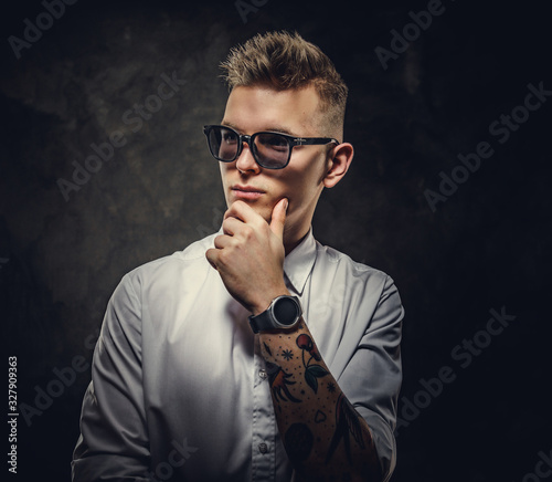 Cool and tattooed hipster male model posing in a studio wearing a white shirt, s Canvas Print