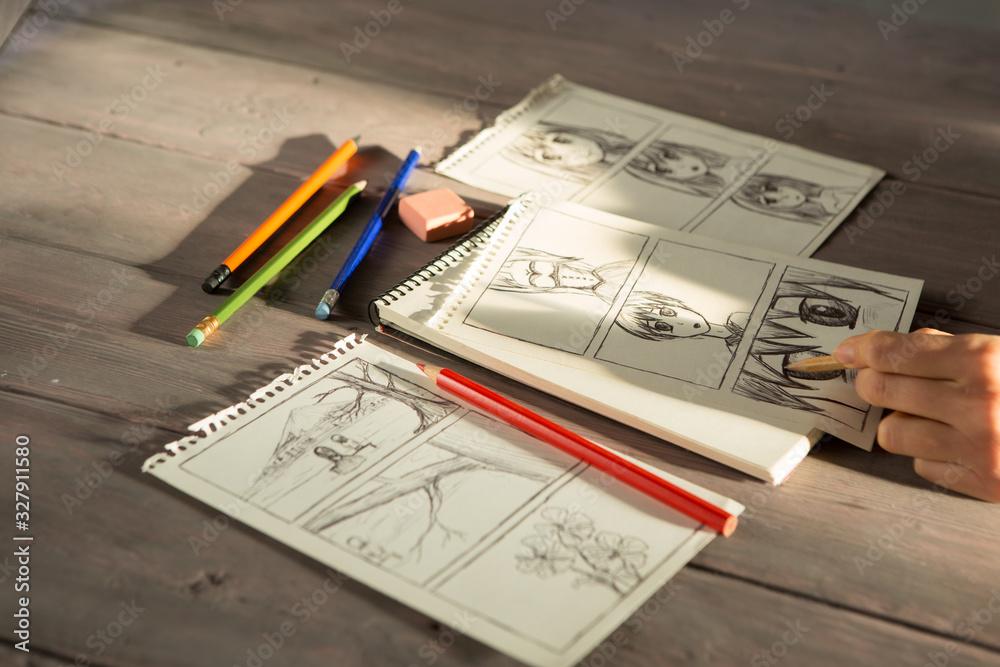 Fototapeta Artist drawing an anime comic book in a studio. Wooden desk, natural light