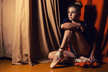 Beautiful Ballet Dancer Sitting On The Stage Of Cross-legged.