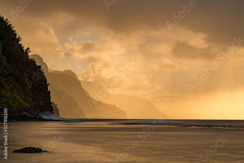 Fototapeta Sunset lights the receding cliffs of the NaPali coastline on north coast of Kauai in Hawaii obraz