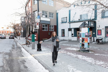 Woman With Smart Phone Hailing Taxi On Snowy City Sidewalk