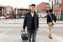 Portrait Confident Senior Man Walking With Suitcase On Urban Street