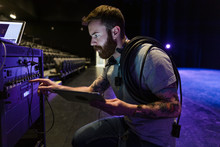 Male Stage Manager Examining Equipment Or Dark Stage