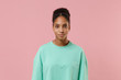 Beautiful young african american woman girl in green sweatshirt posing isolated on pastel pink background studio portrait. People sincere emotion lifestyle concept. Mock up copy space. Looking camera.
