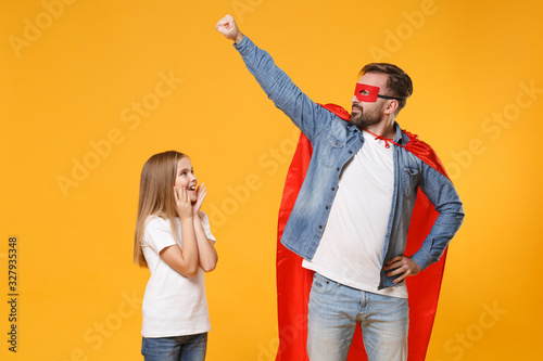 Bearded man in casual clothes Super hero costume have fun with cute child baby girl. Father little kid daughter isolated on yellow background. Love family parenthood childhood concept. Clenching fist.