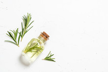 Rosemary Essential Oil In The Bottle On White.