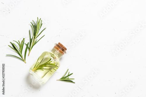 Obraz Rosemary essential oil in the bottle on white. - fototapety do salonu