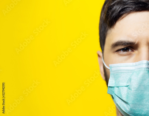 Fototapeta Close-up portrait of male face, wearing medical flu mask on background of yellow color with copy space. obraz