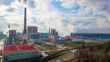 Industrial Paper Mill On Classic Blue Sky Background. Huge Factory. Smoke From The Chimneys. Ecology Problem Concept.