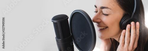 Fényképezés Woman blogger recording radio podcast in studio.