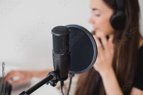 Vászonkép Woman blogger recording radio podcast in studio.
