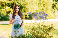 Pretty Young Woman Watering Plants In Summer Garden