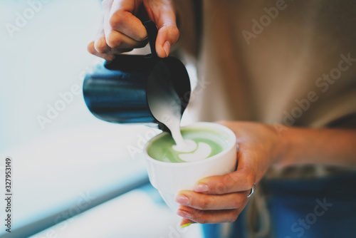 Closeup photo of a woman's hands pouring a milk into a freshly made matcha tea Canvas Print