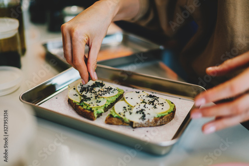 Chef adding pumpkin seeds to delicious vegetarian sandwiches for the breakfast Wallpaper Mural