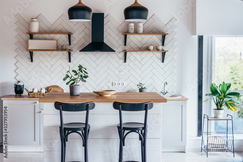 Photo Modern new light interior of kitchen with white furniture and dining table