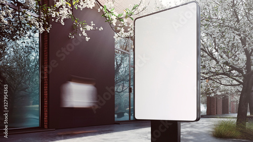 Photo An outdoor blank information board standing on a street with a blooming tree on the background
