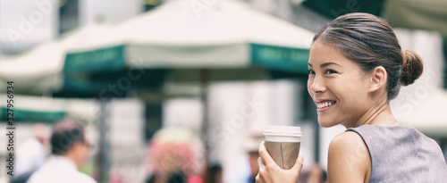 Business woman on office lunch break drinking coffee cup on outdoor summer terrace in New York City park, cafe lifestyle. Happy smiling young professional asian businesswoman.