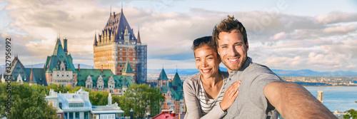 Fototapeta premium Kanada lato podróży turystów para robienie selfie zdjęcie w słynnym mieście Quebec panoramiczny transparent krajobraz. Szczęśliwi młodzi ludzie w zamku Frontenac w Old Quebec.