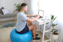 Man Sitting On Fitness Ball Wh...