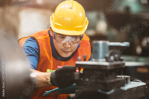 Asian Chinese engineer worker wearing safety suit helmet and eyes protection glasses focus at work inspection and checking production process on factory Wallpaper Mural