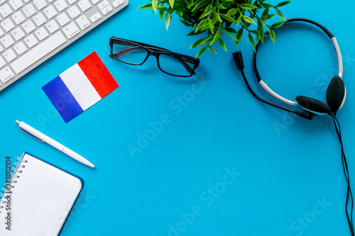 Fototapeta Learn French online. Concept with flag, headset and keyboard on blue background top-down copy space obraz
