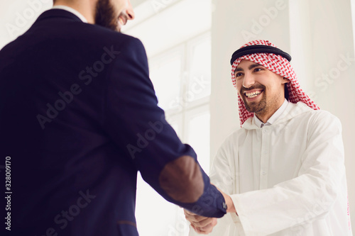 Handshake of arabic and european businesspeople in office. Canvas Print