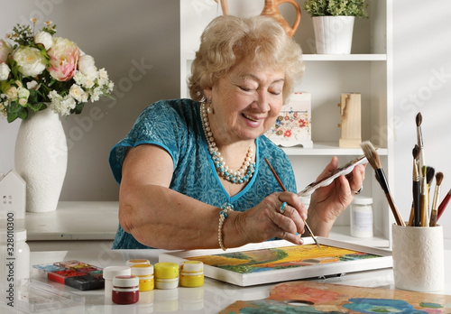 Adult senior woman paints a picture in her studio Canvas