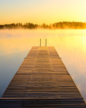 Wooden Dock On A Misty Lake At...