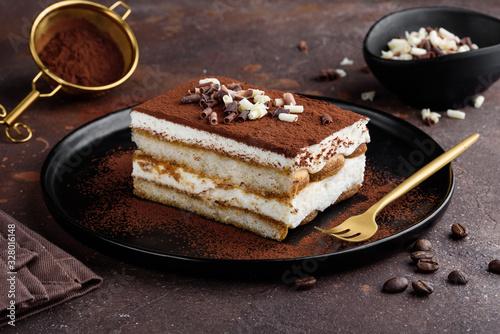 Fototapeta Tiramisu dessert decorated with cocoa and white and dark chocolate on a black plate. Selective focus obraz