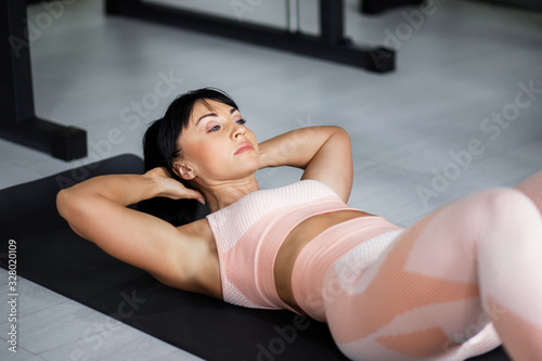 Fototapety, obrazy: Young pretty woman, middle-aged, well-built physique, performs exercises on the press. Active lifestyle