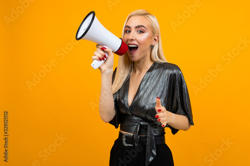 Photo attractive girl in a blouse shouting news in a megaphone on a yellow studio back
