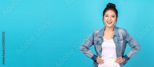 Banner of Happy asian woman standing and feeling happiness and confident on blue background. Cute asia girl smiling or laughing wearing casual travel uniform in jeans shirt and keeping hands on hips